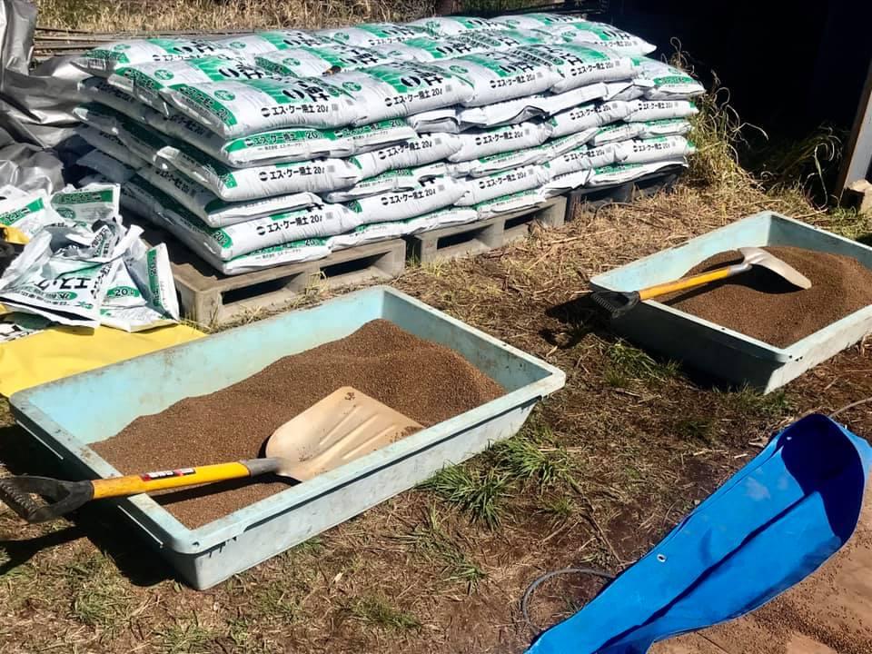 大きなシャベルを使って土と肥料を混ぜます