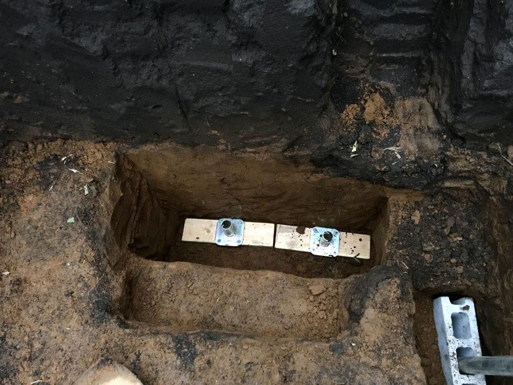 穴に木の板とジョイント金具を設置