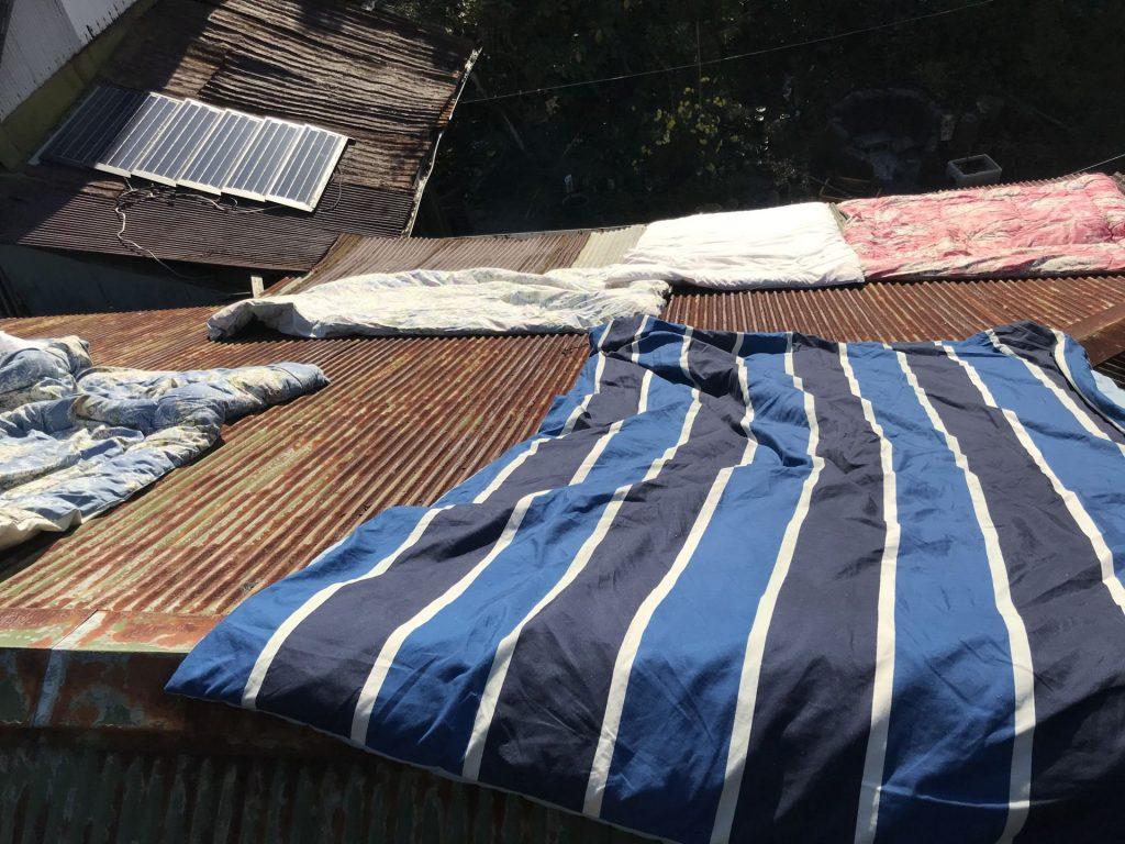 屋根の上で布団干し